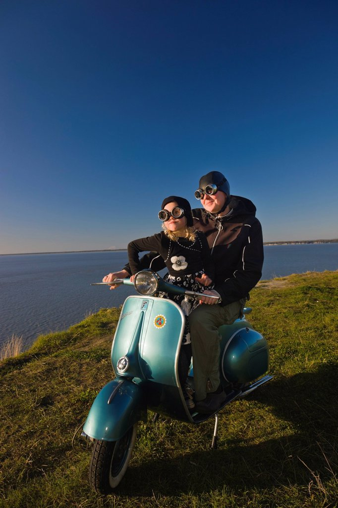 Stock Photo: 4289-13656 Mother and daughter wearing goggles and riding a vintage Vespa, Pt. Woronzof, Cook Inlet, Anchorage, Southcentral Alaska, Summer