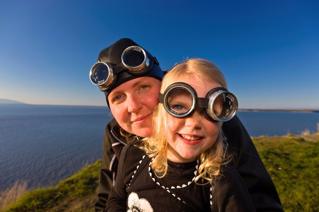 Mother and daughter wearing goggles and riding a vintage Vespa, Pt. Woronzof, Cook Inlet, Anchorage, Southcentral Alaska, Summer : Stock Photo