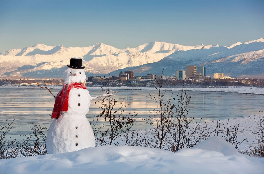 Scenic view of Chugach Mountains, Anchorage skyline, and Cook Inlet with a snowman in the foreground, Southcentral Alaska, Winter : Stock Photo