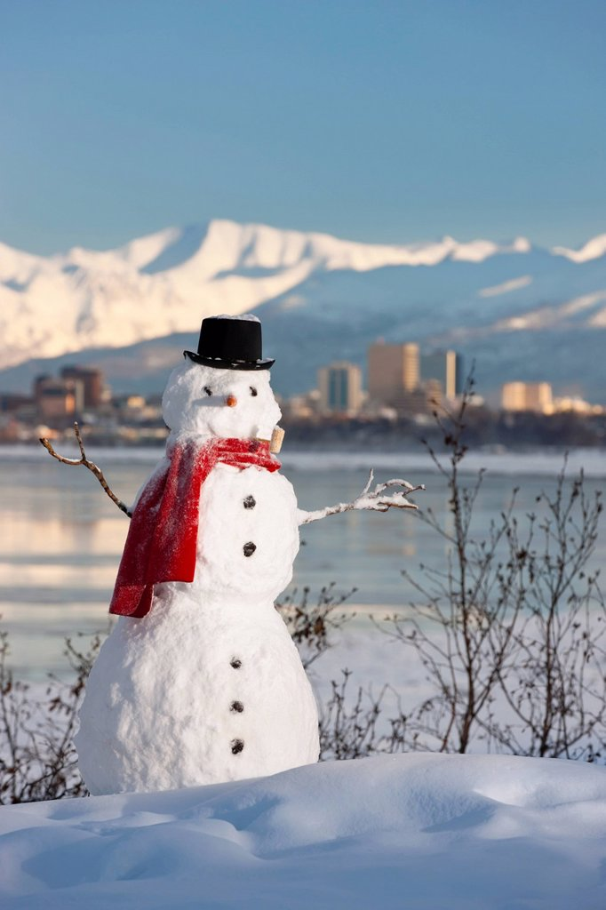 Stock Photo: 4289-13704 Scenic view of Chugach Mountains, Anchorage skyline, and Cook Inlet with a snowman in the foreground, Southcentral Alaska, Winter