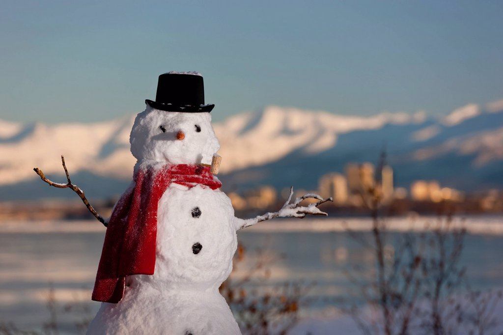 Stock Photo: 4289-13706 Scenic view of Chugach Mountains, Anchorage skyline, and Cook Inlet with a snowman in the foreground, Southcentral Alaska, Winter