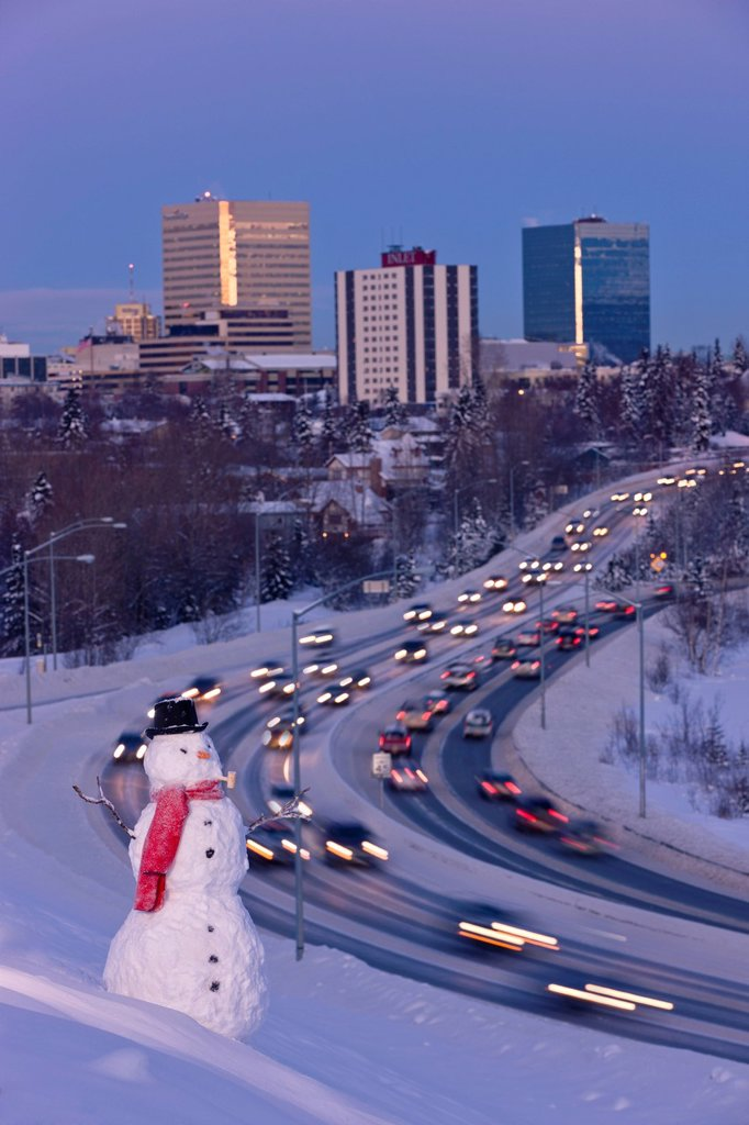 Stock Photo: 4289-13707 View of traffic and downtown Anchorage with a snowman in the foreground, Southcentral Alaska, Winter. Digitally altered.