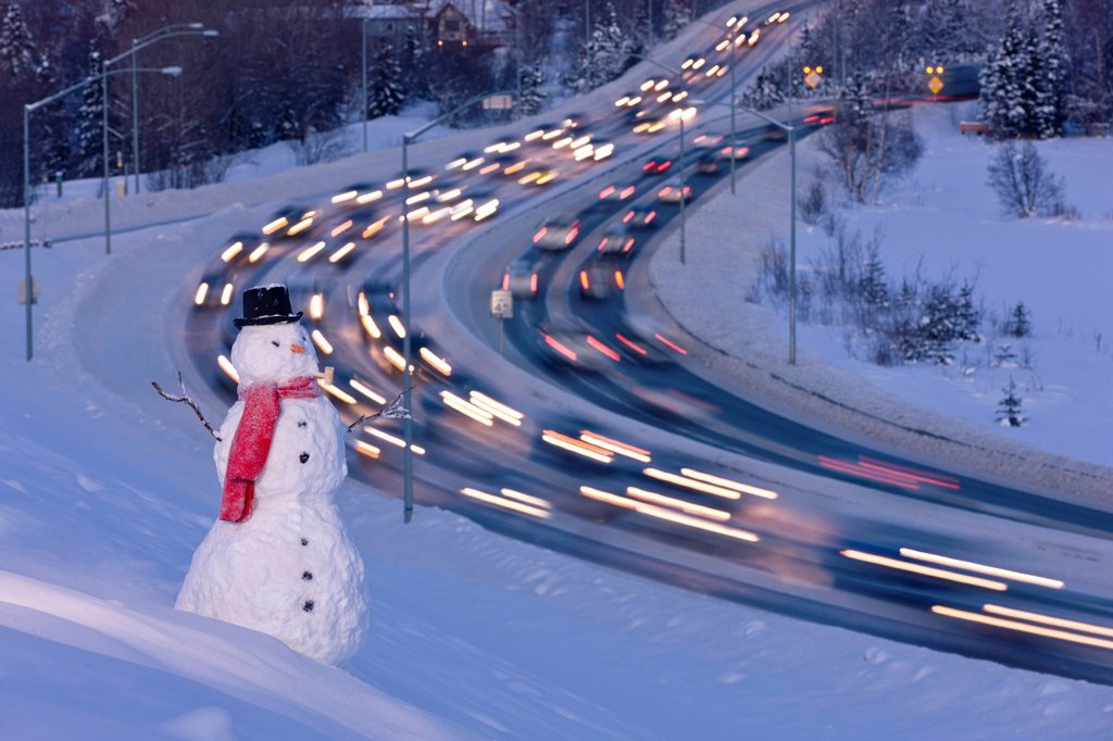 View of traffic near downtown Anchorage with a snowman in the foreground, Southcentral Alaska, Winter. Digital enhanced : Stock Photo