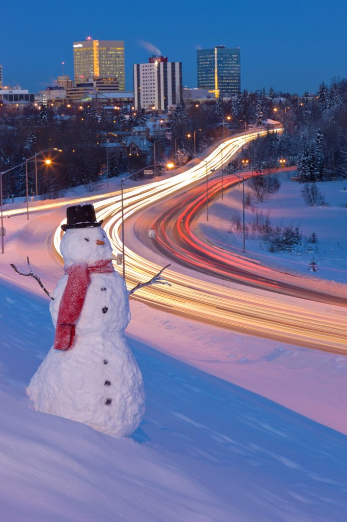 View of traffic and downtown Anchorage with a snowman in the foreground, Southcentral Alaska, Winter. Digitally enhanced. : Stock Photo