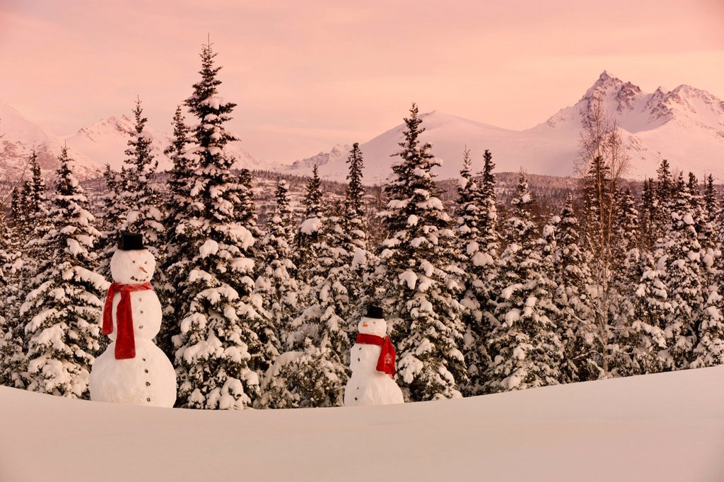 Stock Photo: 4289-13717 Scenic view of Chugach Mountains with an adult and child snowmen wearing a scarf and top hat in the foreground, Anchorage, Southcentral Alaska, Winter