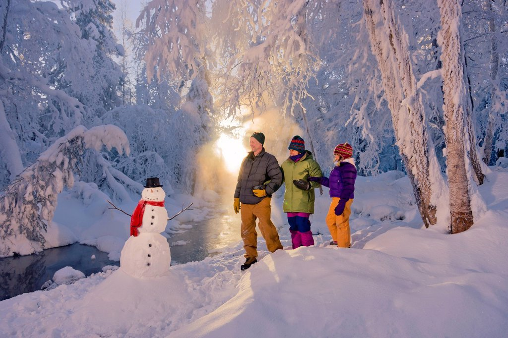 Family stands next to a snowman and small stream in a hoarfrost covered forest, Russian Jack Springs Park, Anchorage, Southcentral Alaska, Winter : Stock Photo