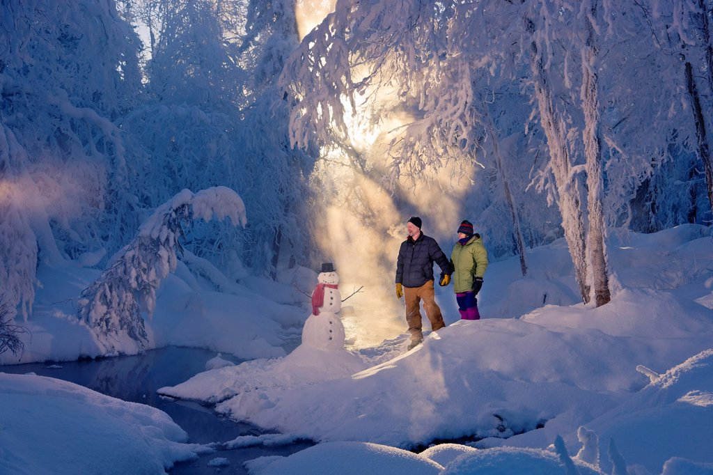 Stock Photo: 4289-13731 Husband and wife standing in a frosty forest next to a snowman and backlit by sunrays, Russian Jack Springs Park, Southcentral Alaska, Winter