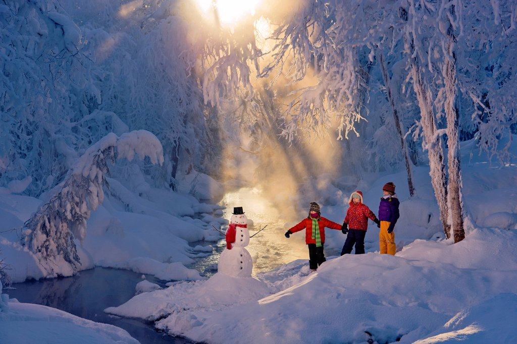 Three children stand and play next to a snowman and stream in a frost covered forest, Russian Jack Springs Park, Anchorage, Southcentral Alaska, Winter : Stock Photo