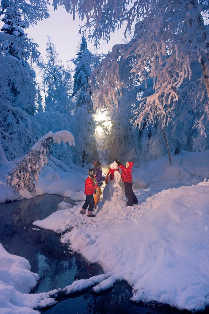 Three children building a snowman next to a stream in a frost covered forest, Russian Jack Springs Park, Anchorage, Southcentral Alaska, Winter : Stock Photo