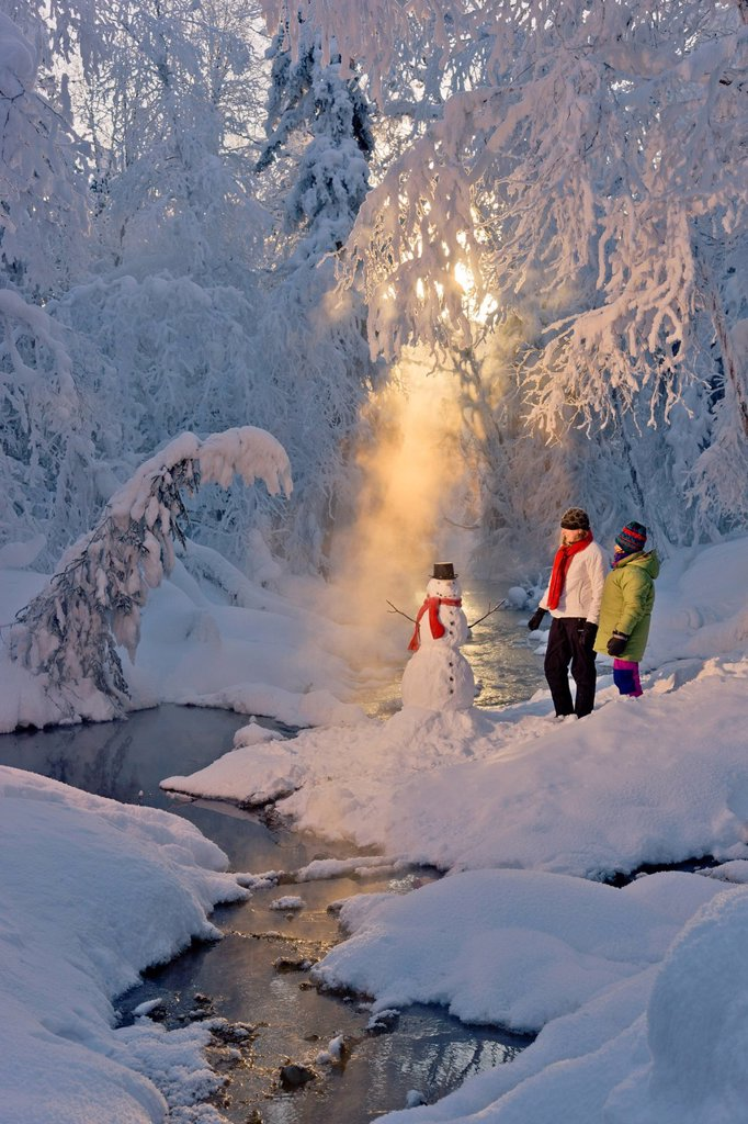 Two woman admire a snowman wearing a red scarf and black top hat next to a small stream in a hoarfrost covered forest, Russian Jack Springs Park, Anchorage, Southcentral Alaska, Winter : Stock Photo