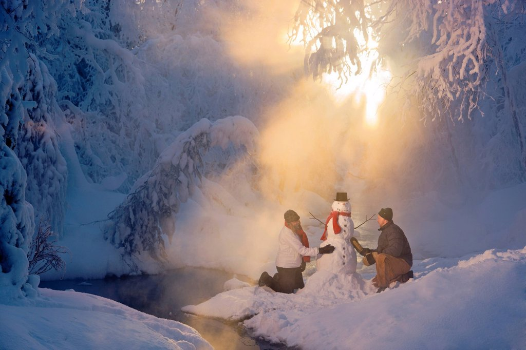 Husband and wife building a snowman in a frosty forest and backlit by sunrays, Russian Jack Springs Park, Southcentral Alaska, Winter : Stock Photo