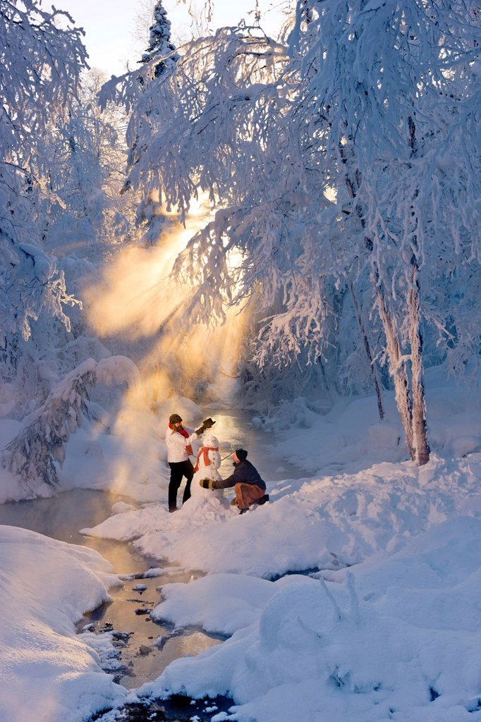 Stock Photo: 4289-13740 Husband and wife building a snowman in a frosty forest and backlit by sunrays, Russian Jack Springs Park, Southcentral Alaska, Winter