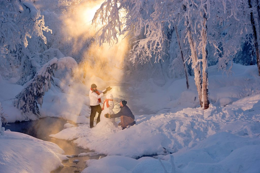 Stock Photo: 4289-13741 Husband and wife building a snowman in a frosty forest and backlit by sunrays, Russian Jack Springs Park, Southcentral Alaska, Winter