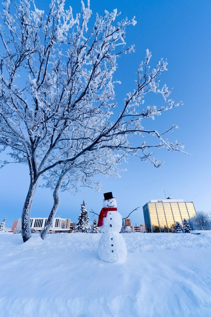 Snowman standing in Delaney Parkstrip with downtown Anchorage in the background at twilight, Southcentral Alaska, Winter. Digitally enhanced. : Stock Photo