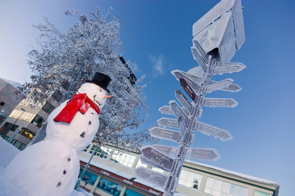 Stock Photo: 4289-13755 Snowman wearing a black top hat and red scarf standing next to the mileage signpost by the visitors log cabin in downtown Anchorage, Southcentral Alaska, Winter. Digitally enhanced
