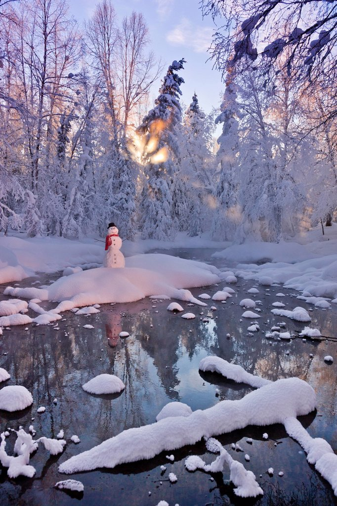 Stock Photo: 4289-13763 Snowman standing on a small island in the middle of a stream with sunrays shining through fog and hoar frosted trees in the background, Russian Jack Springs Park, Anchorage, Southcentral Alaska, Winter. Digitally enhanced.