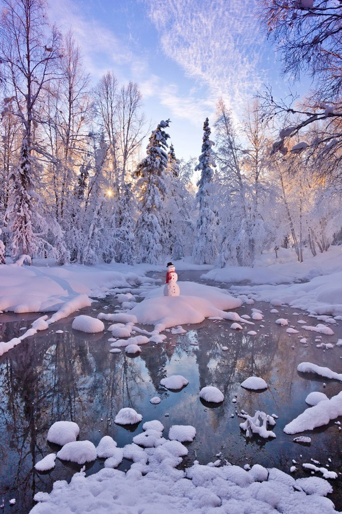 Stock Photo: 4289-13764 Snowman standing on a small island in the middle of a stream with sunrays shining through fog and hoar frosted trees in the background, Russian Jack Springs Park, Anchorage, Southcentral Alaska, Winter. Digitally enhanced.