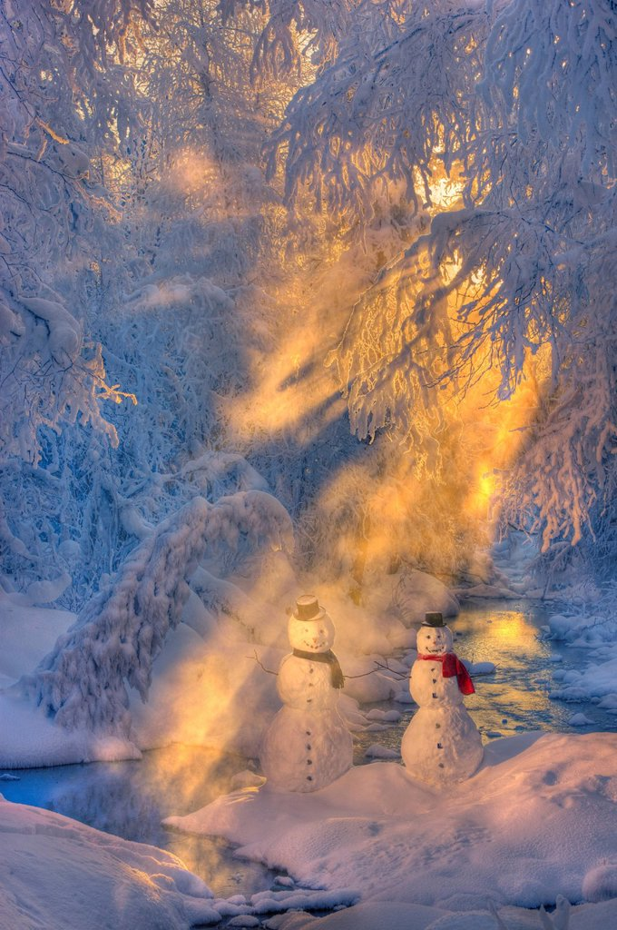 Snowman couple standing next to a stream with sunrays shining through fog and hoar frosted trees in the background, Russian Jack Springs Park, Anchorage, Southcentral Alaska, Winter. Digitally enhanced. : Stock Photo