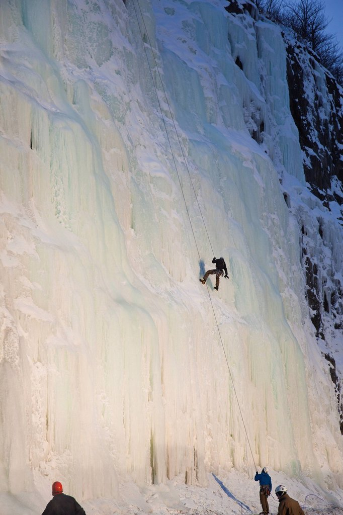 Stock Photo: 4289-13853 Evening light shines on an ice climber as he repels down an ice waterfall along Turnagain Arm, Southcentral Alaska, Winter