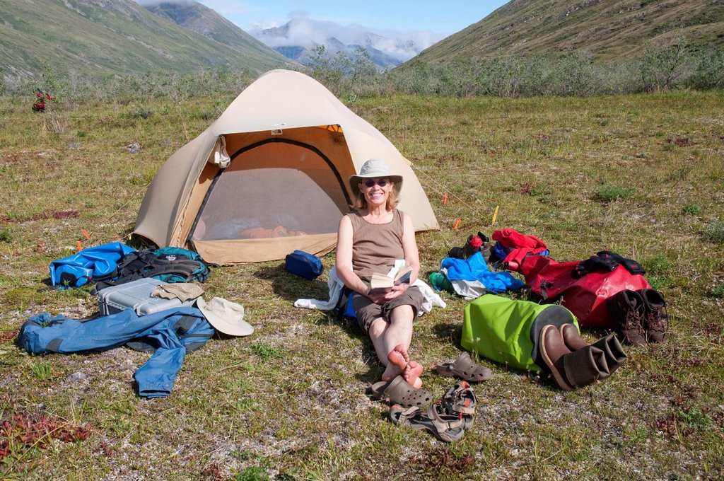 Stock Photo: 4289-13867 Mature female camper relaxes by tent on a sunny day on the Marsh Fork of the Canning River in the Brooks Range, Arctic National Wildlife Refuge, Alaska, Summer