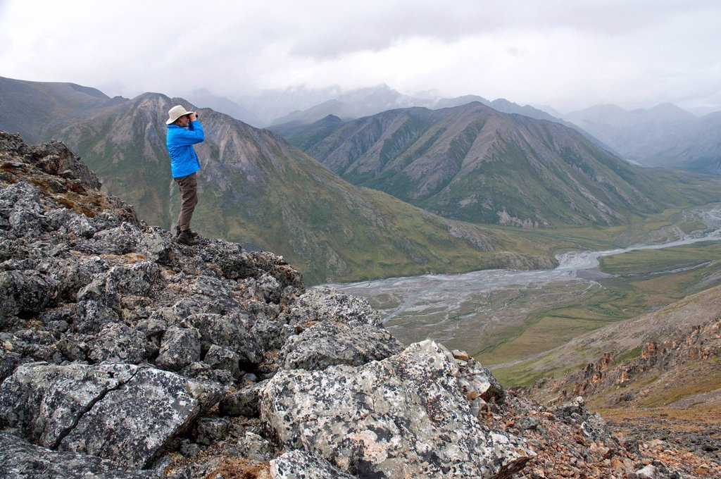 Stock Photo: 4289-13869 Mature female hiker on a rock glassing the landscape above the Marsh Fork of the Canning River in the Brooks Range, Arctic National Wildlife Refuge, Alaska, Summer