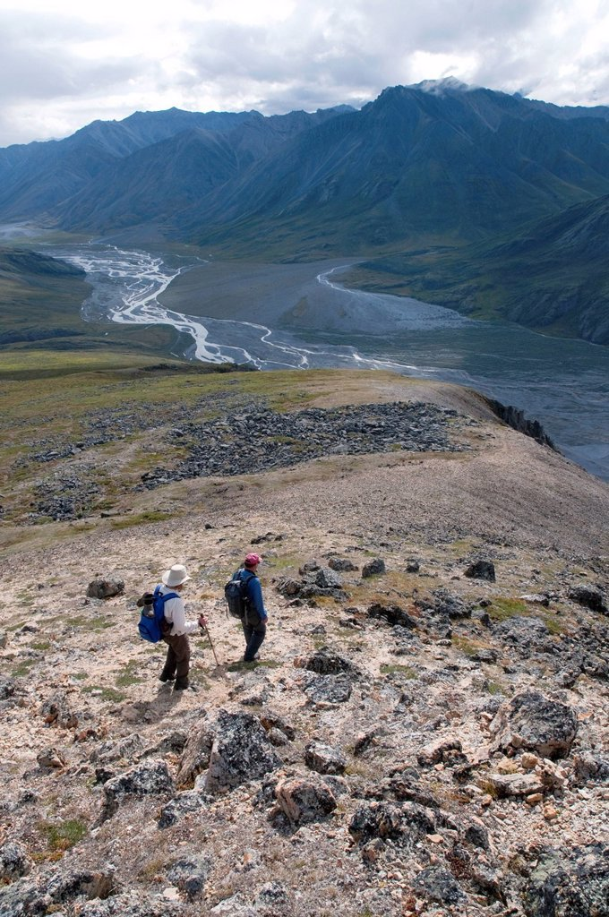Mature hikers descend a ridge above the Marsh Fork of the Canning River in the Brooks Range, Arctic National Wildlife Refuge, Alaska, Summer : Stock Photo