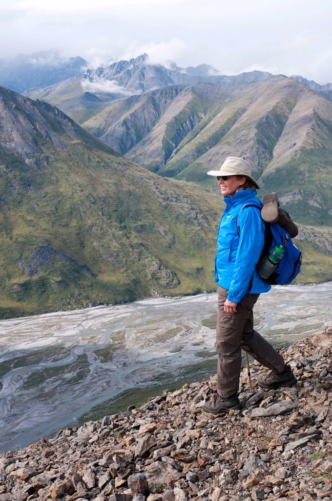 Mature female hiker descends ridge above the Marsh Fork of the Canning River in the Brooks Range, Arctic National Wildlife Refuge, Alaska, Summer : Stock Photo
