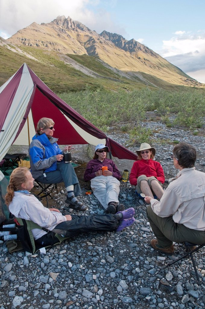 Mature female hikers relax at campsite along the Marsh Fork of the Canning River in the Brooks Range, Arctic National Wildlife Refuge, Alaska, Summer : Stock Photo