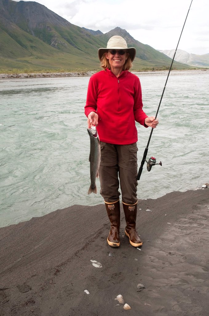 Stock Photo: 4289-13884 Mature woman squatting with fishing pole shows off Dolly Varden Char caught in the Canning River, Brooks Range, Arctic National Wildlife Refuge, Alaska, Summer