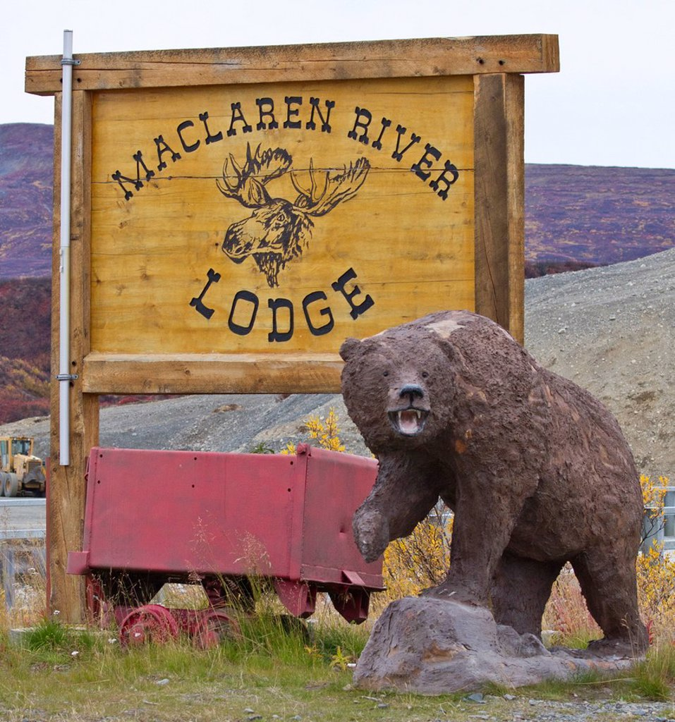 Stock Photo: 4289-14045 Maclaren River Lodge sign, with mining rail cart and carved brown bear, Denali Highway, Southcentral Alaska, Autumn