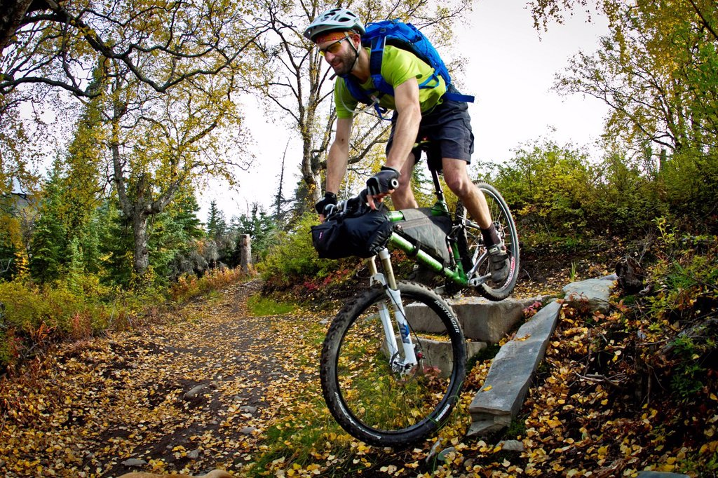 Man mountain biking over rocks, Anchorage hillside trails, Southcentral Alaska, Autumn : Stock Photo