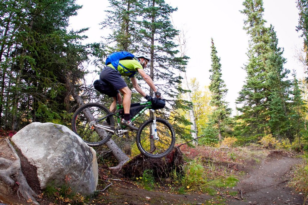 Stock Photo: 4289-14090 Man mountain biking over rocks, Anchorage hillside trails, Southcentral Alaska, Autumn