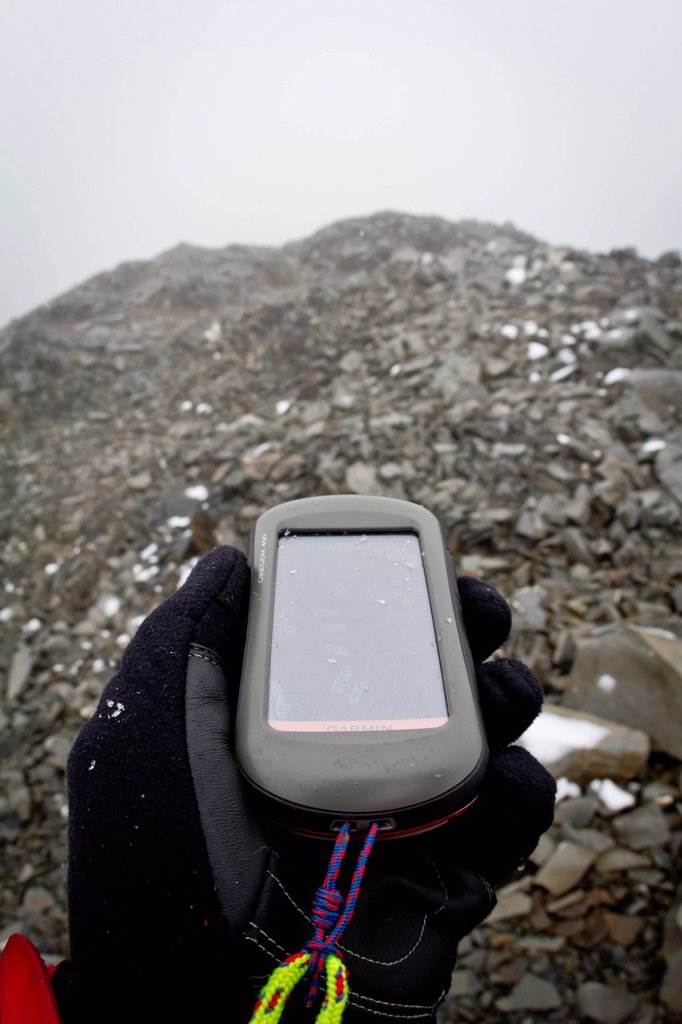 View of a hand holding a GPS and navigating a fog whiteout on a rocky ridge between the Ruth Glacier and Tokositna Glacier, Denali National Park & Preserve, Alaska Range, Interior Alaska, Autumn : Stock Photo