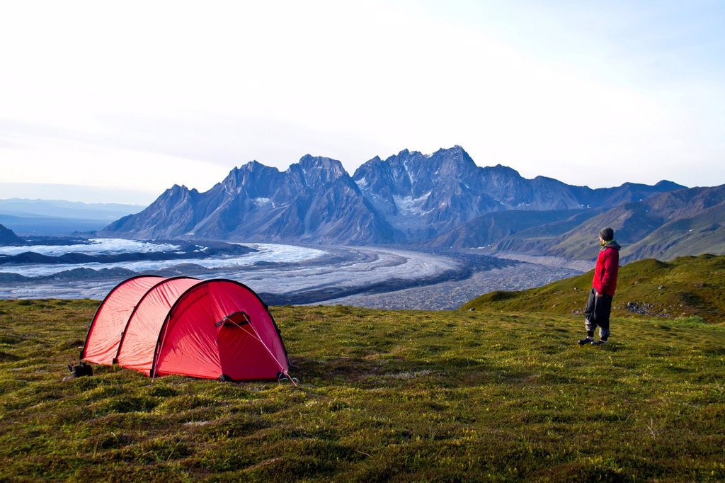 Male backpacker at camp above the Ruth Glacier with the Tokosha Mountains beyond, Denali National Park & Preserve, Interior Alaska, Autumn : Stock Photo