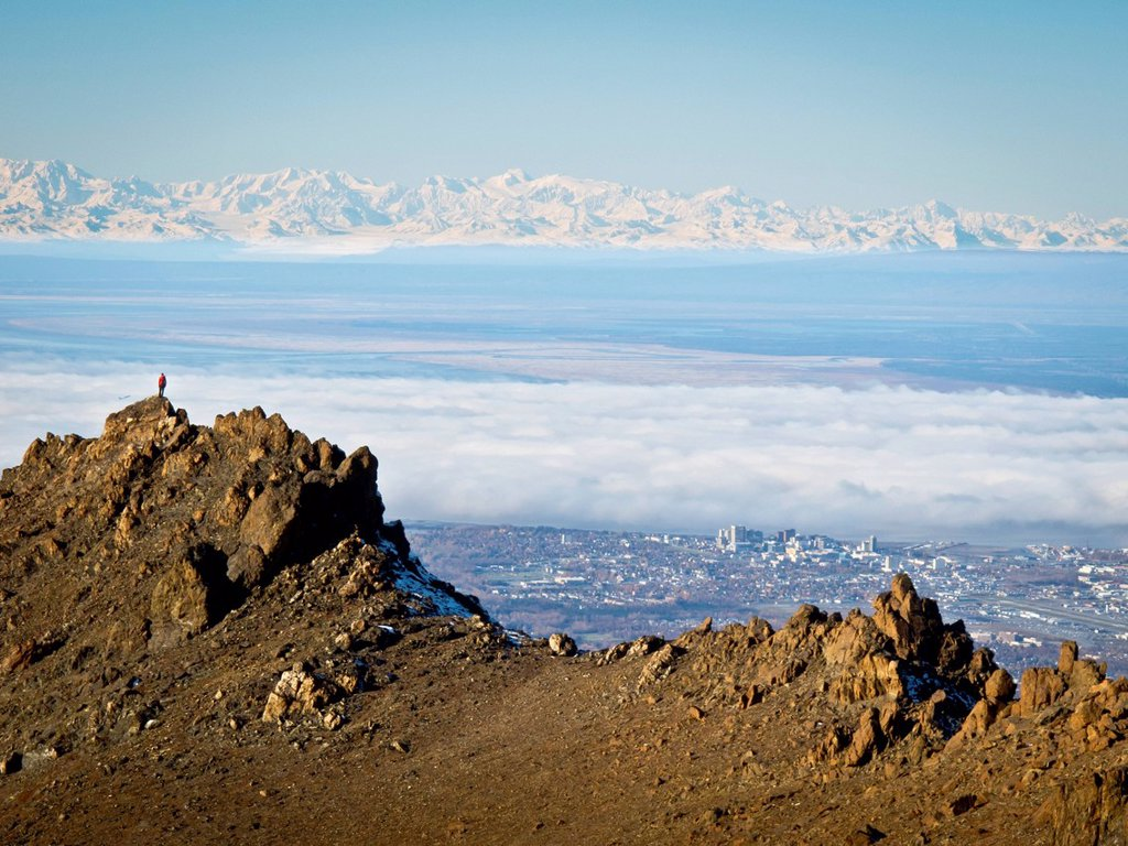 Woman trail runner stands on a rock ridge high above Anchorage with the Alaska Range beyond, Chugach Mountains, Southcentral Alaska, Autumn : Stock Photo