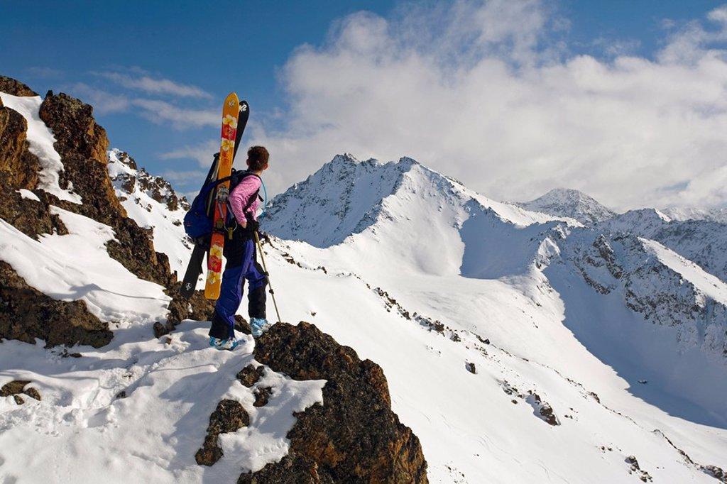 Woman Telemark Skier stands on ridge viewing Mount Tikishla Chugach Mountains & State Park Alaska Winter : Stock Photo