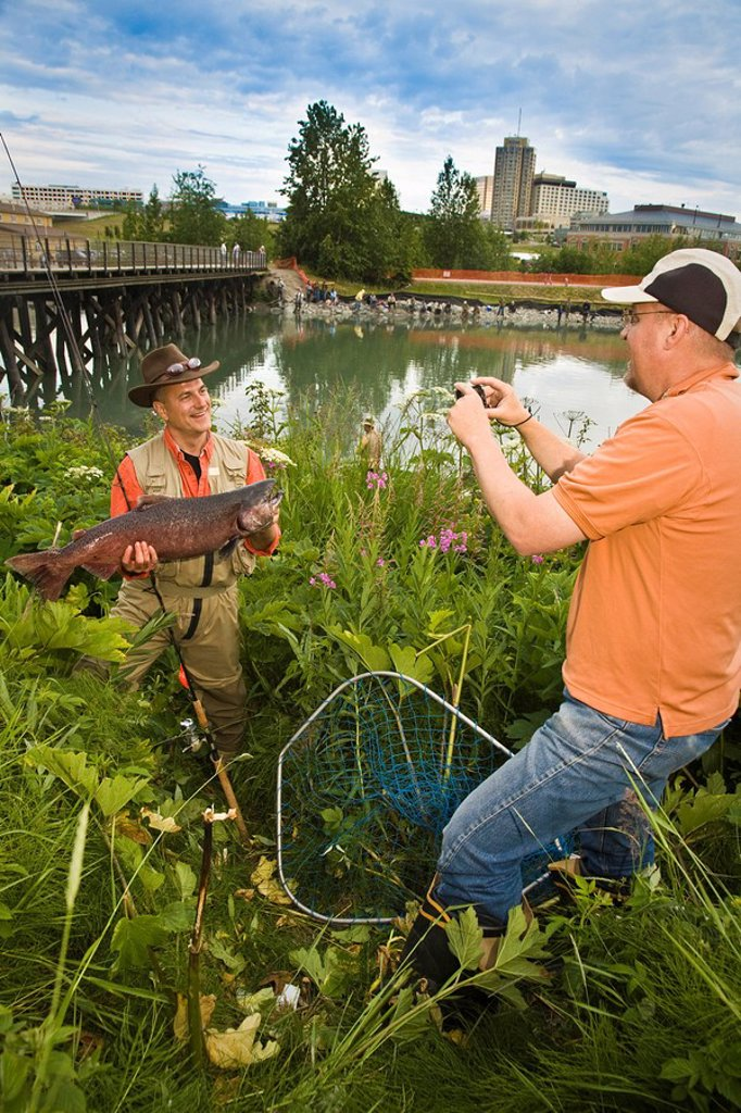 Stock Photo: 4289-15758 Fisherman poses with King Salmon at Ship Creek in downtown Anchorage, Alaska during Summer