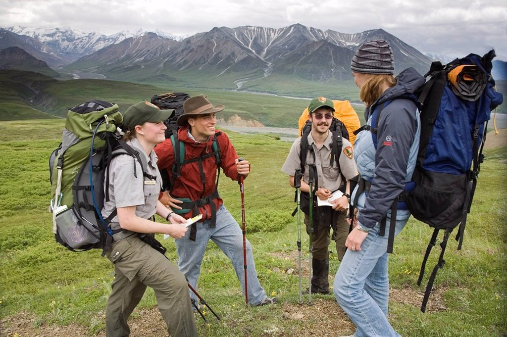 National Park Rangers talk to a couple of backpackers in Denali National Park Alaska : Stock Photo
