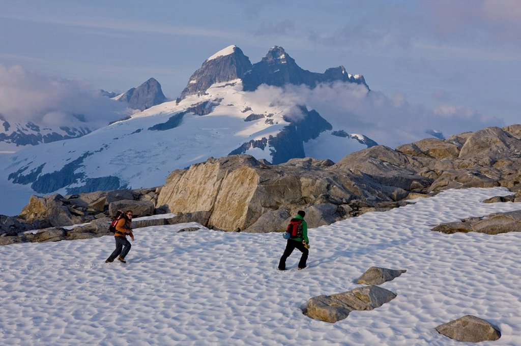 Hikers climb in the afternoon sun on a ridge above the Juneau Ice Field, Juneau, Alaska, Tongass National Forest : Stock Photo