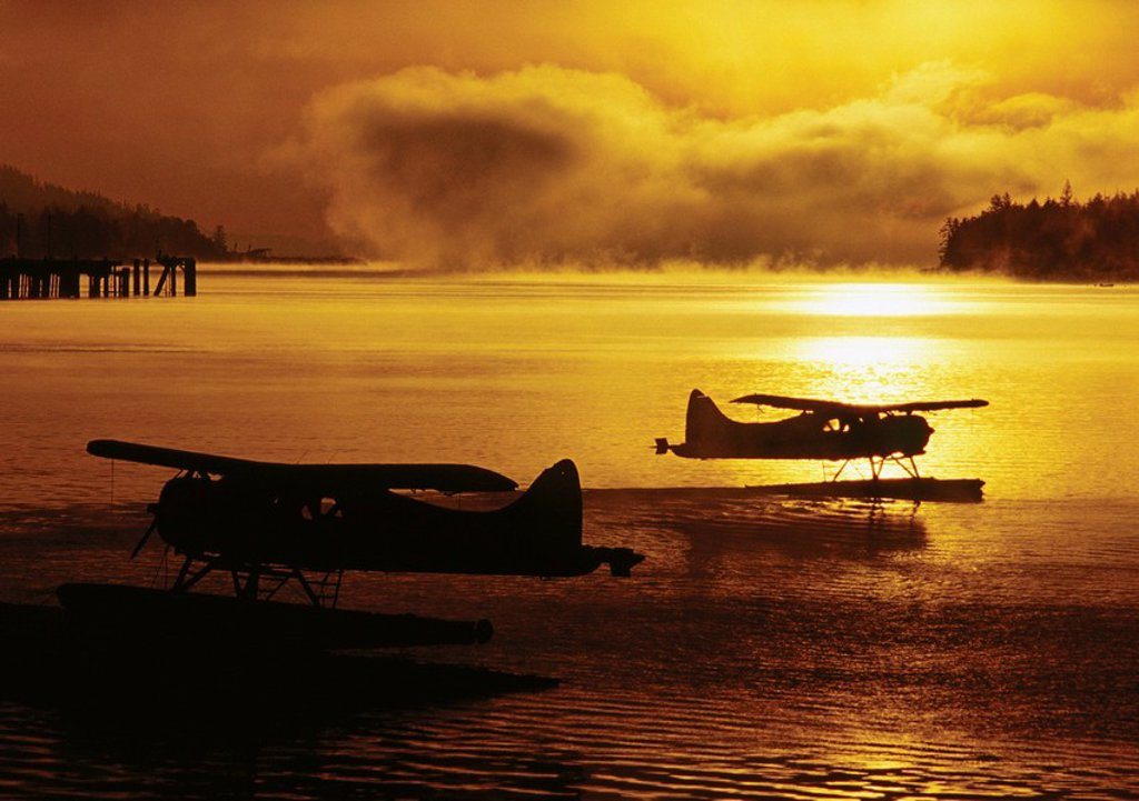 Silhouette of deHavilland Beaver floatplanes at sunset in the Tongass Narrows, Ketchikan, Alaska. : Stock Photo
