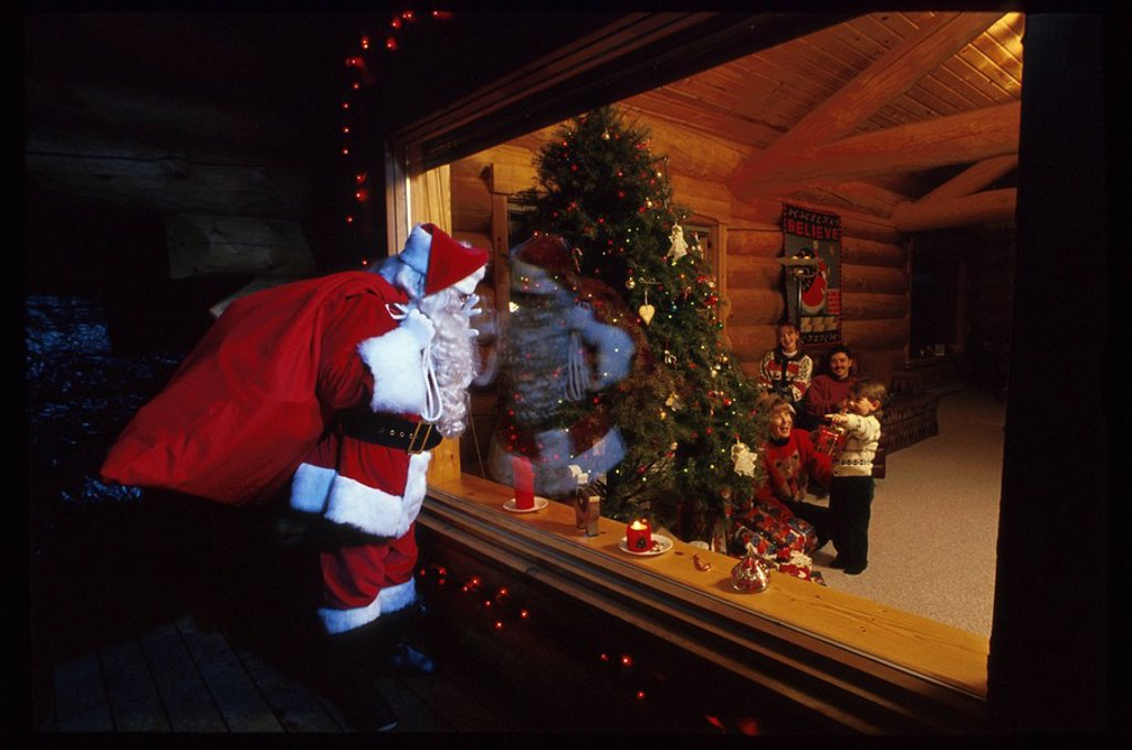 Santa Claus Looking in Cabin Window at Family Girdwood Ak Christmas Tree Southcentral : Stock Photo