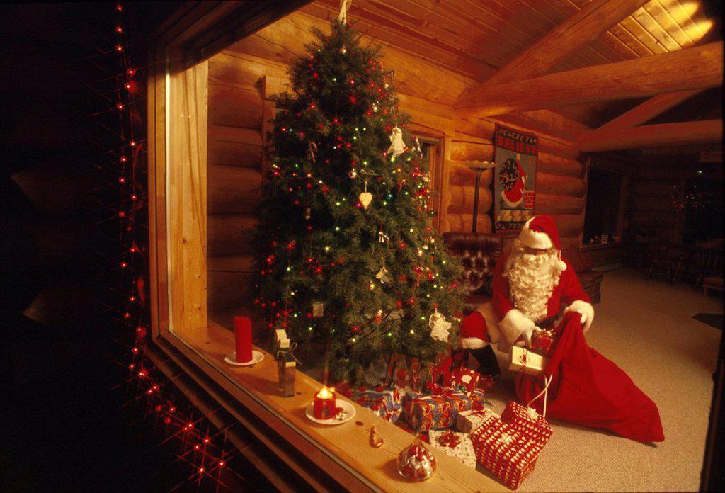 Stock Photo: 4289-28117 Santa Claus Giving Presents Christmas Tree Girdwood AK Southcentral Winter Cabin