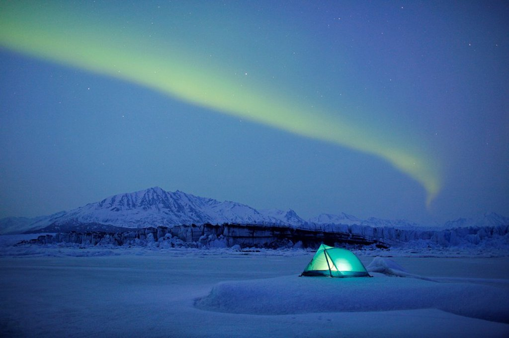Northern Lights over lit tent on Knik Glacier, Southcentral, Alaska, Winter : Stock Photo