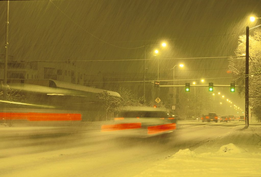 Stock Photo: 4289-32117 Cars Driving City Street Snowing Winter Night ANC AK Southcentral Blurred