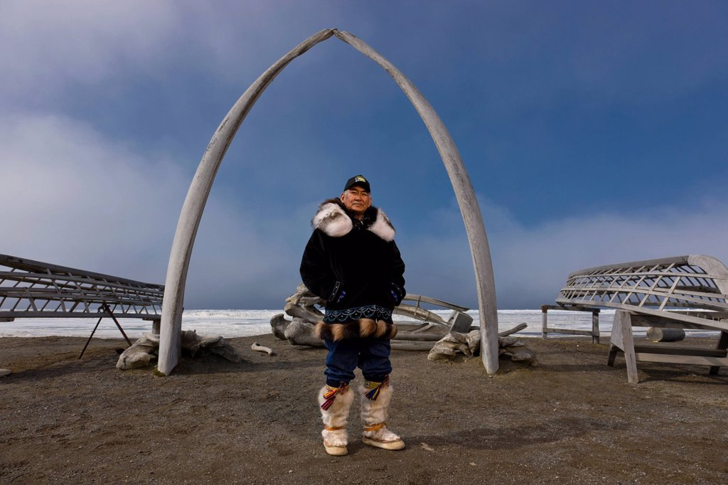 Stock Photo: 4289-34607 Male Inupiaq Eskimo hunter wearing his Eskimo parka Atigi, seal skin hat and wolf skin Maklak´s with soles made from bearded seal skin Ugruk standing in front of a Bowhead whale bone arch and Umiaqs, Barrow, Arctic Alaska, Summer
