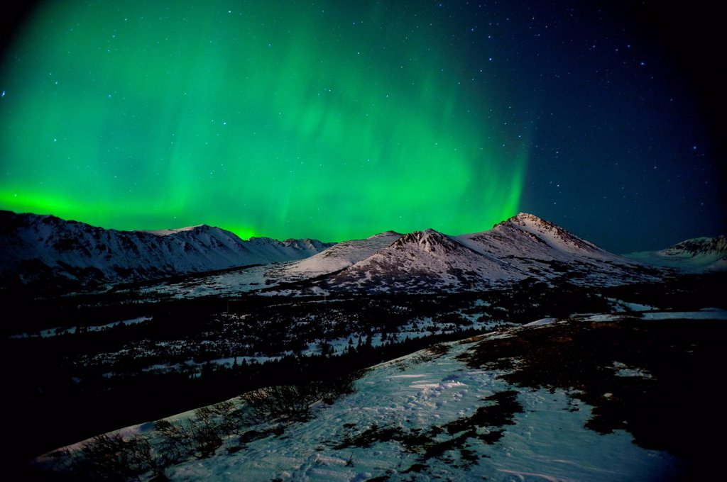 The Northern Lights over Wolverine Peak in the Chugach State Park near Powerline Pass, Anchorage, Southcentral Alaska, Winter : Stock Photo