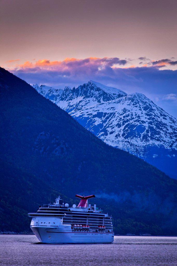 Carnival Cruise Spirit sailing through Lynn Canal at sunset, near Haines, Inside Passage, Southeast Alaska, Summer : Stock Photo