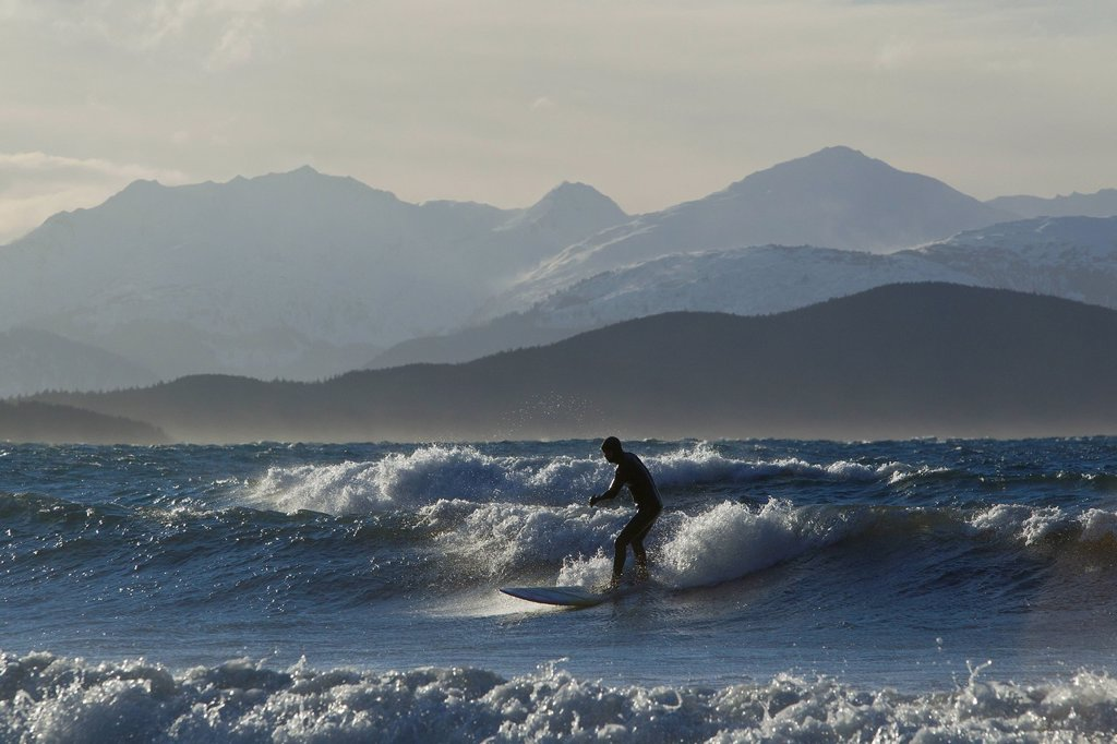 Stock Photo: 4289-9336 Man surfing along the coastline in Winter with Chilkat Range in the background, Eagle Beach, Southeast Alaska