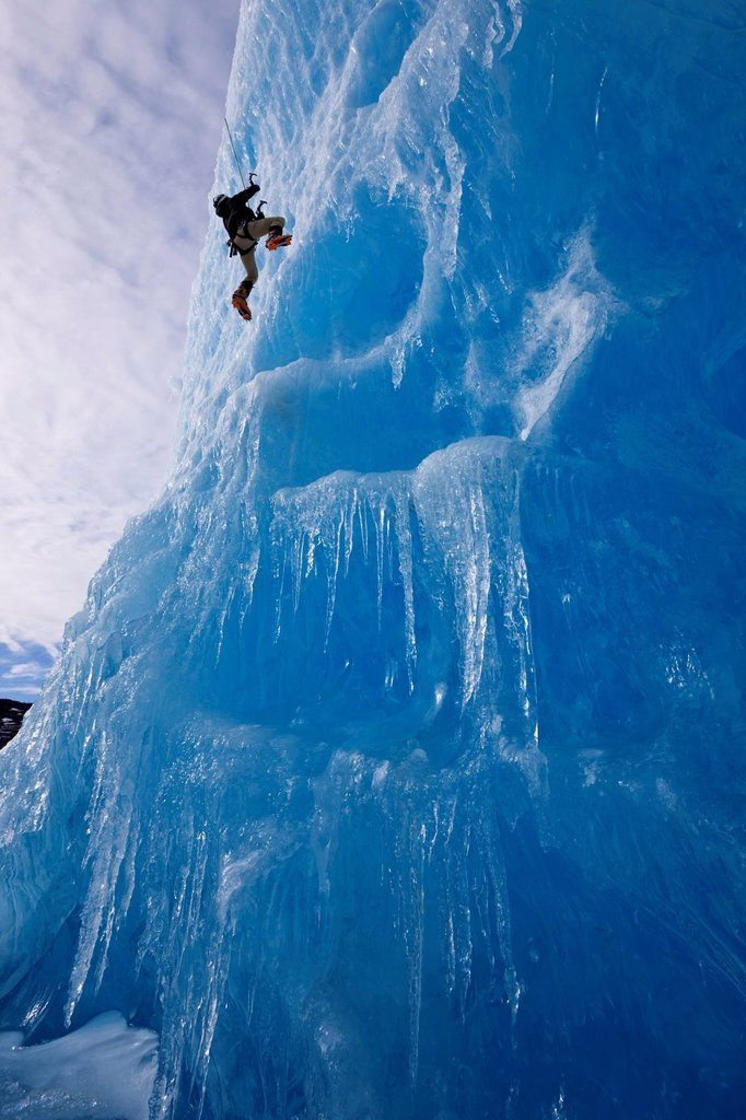 An ice climber ascends the face of a large iceberg frozen into Mendenhall Lake, Juneau, Southeast Alaska, Winter : Stock Photo