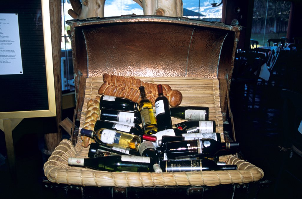 Display of bottles of wine and bread in basket, Puno, Peru : Stock Photo